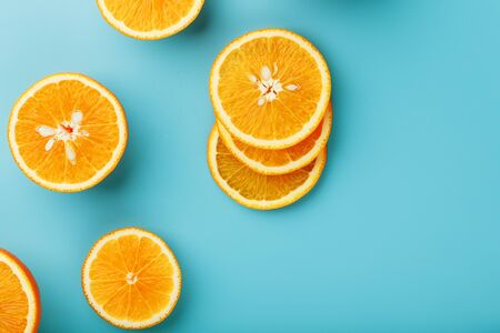 Round slices of juicy orange on a blue background, top view as a background substrate. Food background. Citrus pattern, flat lay
