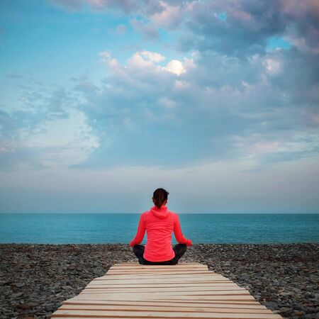 The girl meditates and practices yoga on the beach. Against the backdrop of a sunset pink sky with golden clouds. In a pink sweater with a wooden walkway to the sea.