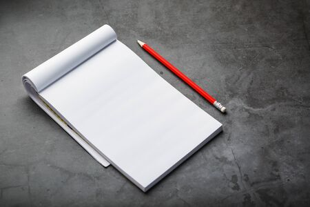 Notepad with a red pencil on a black stone plate background, for education, recording goals and deeds. Free white space for writing on a blank sheet of notebook, concept.