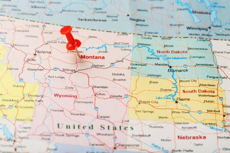 Red clerical needle on a map of USA, Montana and the capital of Helena. Close up Montana map with red tack US map pin