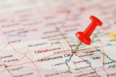 Red clerical needle on a map of the USA, Oklahoma and the Capital of Oklahoma City. Close up map of Oklahoma with red tack, US map pin