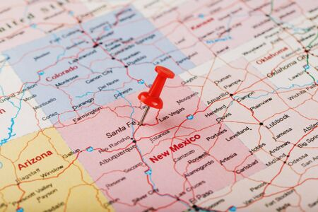 Red clerical needle on a map of USA, New Mexico and the capital of Santa Fe. Close up map of new mexico with red tack, US map pin