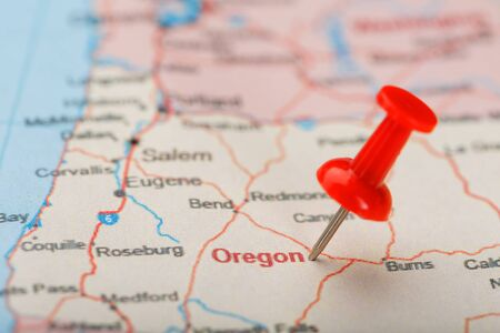 Red clerical needle on a map of USA, Oregon and the capital Salem. Closeup Map Oregon with Red Tack, US map pin