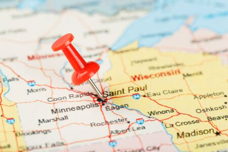 Red clerical needle on a map of USA, Minnesota and the capital Saint Paul. Close up map of Minnesota with red tack 免版税图像
