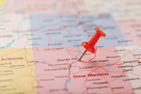 Red clerical needle on a map of USA, New Mexico and the capital of Santa Fe. Close up map of new mexico with red tack