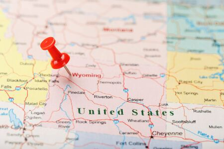 Red clerical needle on a map of USA, Wyoming and the capital Cheyenne. Close up map of wyoming with red tack, US map pin Фото со стока