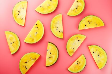 Slice of Yellow watermelon on a pink background. Bright summer background. Minimal food concept idea. Flat lay, top view. 写真素材