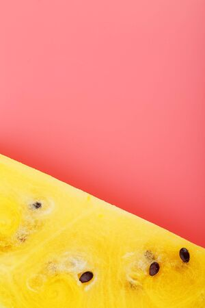 Slice of Yellow watermelon on a pink background. Bright summer background, copy space 写真素材