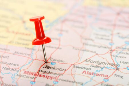 Red clerical needle on a map of USA, South Mississippi and the capital Jackson. Close up map of South Mississippi with red tack, United States map pin USA