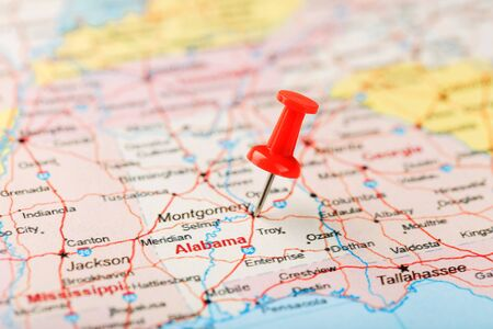 Red clerical needle on a map of USA, South Alabama and the capital Montgomery. Close up map of South Alabama with red tack, United States map pin USA