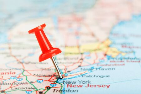 Red clerical needle on a map of USA, South New Jersey and the capital New York. Close up map of South New Jersey with red tack, United States map pin USA