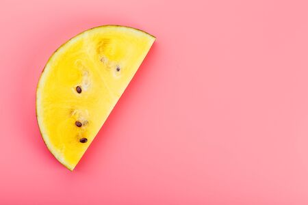 Juicy slices of yellow watermelon on a bright pink background. Conceptual colors of summer. Patterns top view as a background or substrate, wallpaper 写真素材