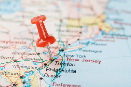 Red clerical needle on a map of USA, South New Jersey and the capital Trenton. Close up map of South New Jersey with red tack, United States map pin USA