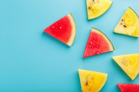 Slices of fresh pieces of yellow and red watermelon on a blue background. Free place. View from above 版權商用圖片 - 129172678