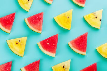 Summer pattern of red fruit watermelon slices of red and yellow on a light blue background. Minimal summer concept. Fashionable color of the sun 版權商用圖片 - 129172682