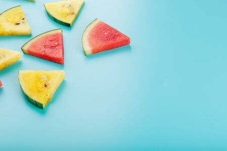 Slices of fresh pieces of yellow and red watermelon on a blue background. Free place. View from above 版權商用圖片