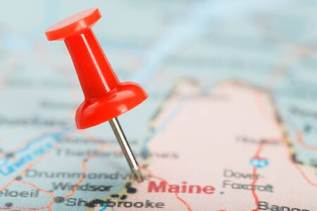 Red clerical needle on a map of USA, South South Maine and the capital Augusta. Close up map of South South Maine with red tack, United States map pin USA