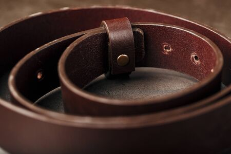 Fashionable men's brown belt made of genuine leather with a light metal buckle on a dark background. Genuine leather, handmade. Close-up Stockfoto
