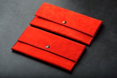 A pair of red genuine leather wallets with rivets on a dark background top view. Genuine leather, handmade