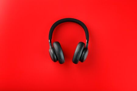 Wireless black headphones on a red background. View from above. In-ear headphones for playing games and listening to music tracks. Modern style