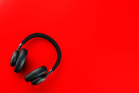 Black wireless headphones on a red background. Overhead, isolated professional-grade headphones for DJs and musicians. View from above. 스톡 콘텐츠