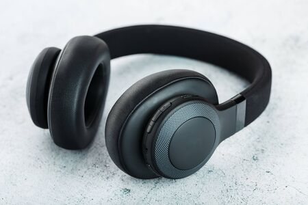 Wireless Black Headphones on a gray stone background. View from above. In-ear headphones for playing games and listening to music tracks. Modern style