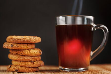 A pile of oatmeal cookies with chocolate chips and a mug of fragrant black hot tea in on a bamboo substrate, on a dark background. Handmade cookies for a healthy breakfast. Close-up