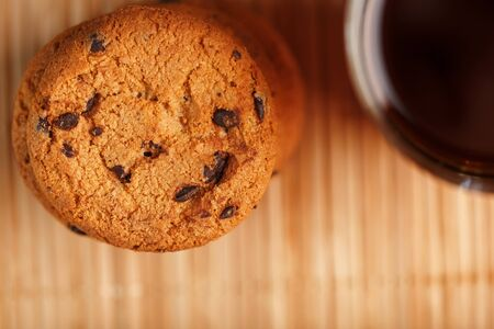 A pile of oatmeal cookies with chocolate chips and a mug of fragrant black hot tea in on a bamboo substrate, on a dark background. Handmade cookies for a healthy breakfast. Top view