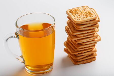 A stack of golden wheat cookies and a mug of fragrant green tea in on a white background. Cookies laid out in a breakfast column and a golden highlight with tea mugs. Close-up, isolate