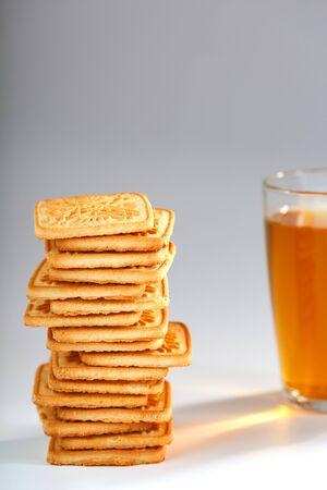 A stack of golden wheat cookies and a mug of fragrant green tea in on a gray background. Cookies laid out in a breakfast column and a golden highlight with tea mugs. Close-up, isolate