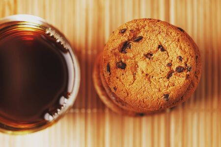 Oatmeal cookies with chocolate pieces and a mug of aromatic black tea in on a bamboo substrate, Low contrast. Close-up