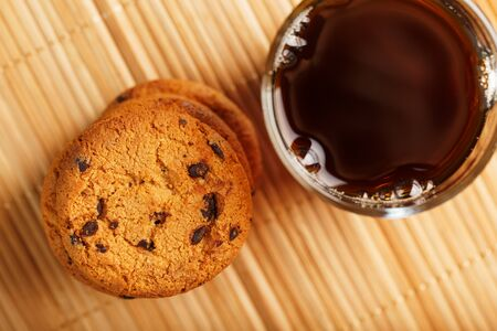 Oatmeal cookies with pieces of chocolate and a mug of coffee on a bamboo stand. Close-up, top view Stock Photo