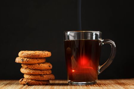 Oatmeal cookies with pieces of chocolate and a mug of coffee on a bamboo stand. Close-up