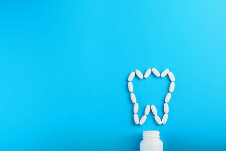 White Vitamins with calcium Ca, D3 in the form of a tooth scattered from a white jar on a blue background. The concept of pharmaceuticals and dentistry, dental care.