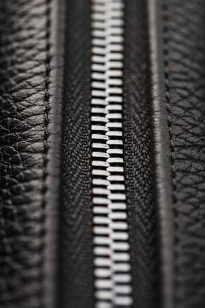 Close-up of the lock on a bag made of genuine black leather, on a dark background. Macro close up