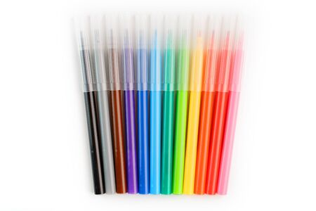 Multi-colored felt-tip pens, markers on a white isolated background. Rainbow colors overall plan, top view.