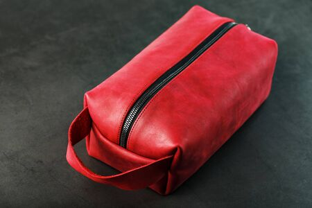 Bag for cosmetics and jewelry made of genuine red leather, on a dark background. Handwork, View from above Archivio Fotografico - 130038386