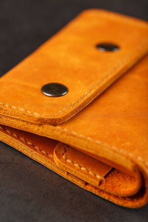 Brown purse, wallet made of genuine leather on a dark background. Elements of leather craft products handmade. Handmade rivets and seam Close-up