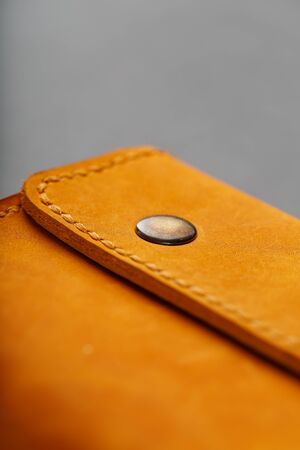 Brown purse, wallet made of genuine leather Nubuck on a dark background. Elements of leather craft products handmade. Handmade rivets and seam Close-up