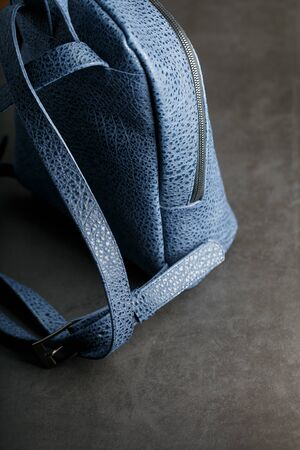Blue backpack made of genuine leather on a dark background, handmade. Close up and in detail.