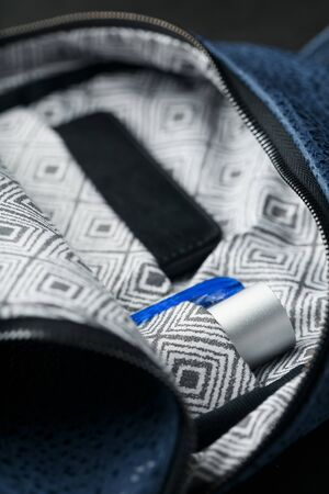 Close-up inside pockets, elements of a blue backpack made of genuine leather on a dark background, handmade. Macro