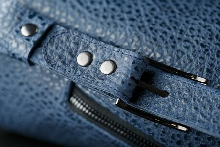 Lock and buckle close-up, elements of a blue backpack made of genuine leather on a dark background, handmade. Macro