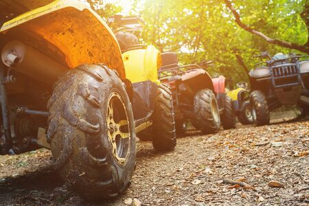 A group of ATVs in a forest covered in mud. Wheels and elements of all-terrain vehicles in mud and clay. Active leisure, sports and tourism. Extreme