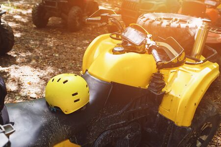 Casco amarillo en un ATV en el bosque, en el barro. Ruedas y elementos de vehículos todo terreno en barro y arcilla. Ocio activo, deporte y turismo. Extremo Foto de archivo