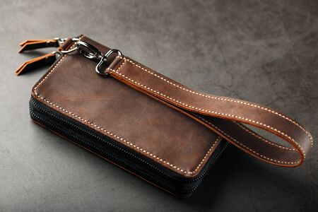 Organizer wallet made of brown Genuine leather, handmade on a dark background. Close-up, castle and carbines. View from above. Stock Photo