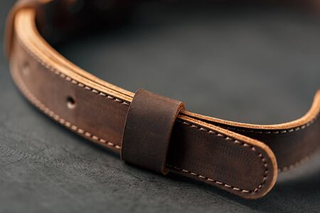 Brown belt made of genuine brown leather handmade on a dark background. Close-up Foto de archivo