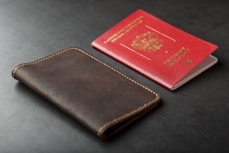 Brown leather cover with a red passport on a dark background. Russian Federation, handwork close-up. Фото со стока