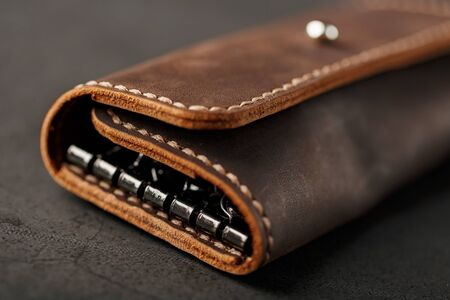 Wallet Keymaster made of brown Genuine leather, handmade on a dark background. Close-up Stock Photo