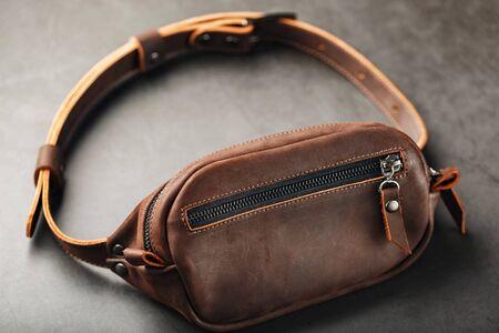 Handmade genuine brown leather on a dark background Brown belt bag. Elegant brown bag with a zipper. Banana bag
