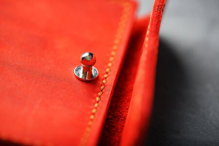 Handmade key holder made of genuine red leather on a dark background. Close-up